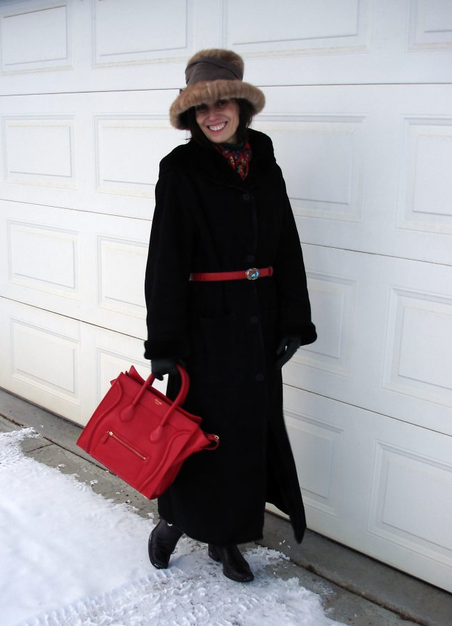 stylist in hooded maxi shearling coat, hat, belt bag, tall boots