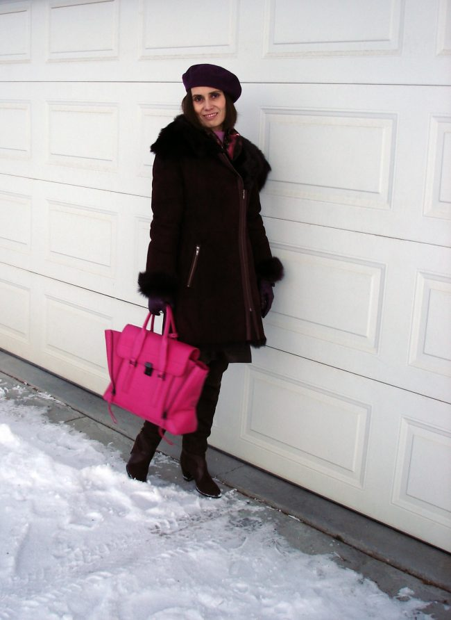style book author in motorcyle shearling coat with beret and fuchsia bag