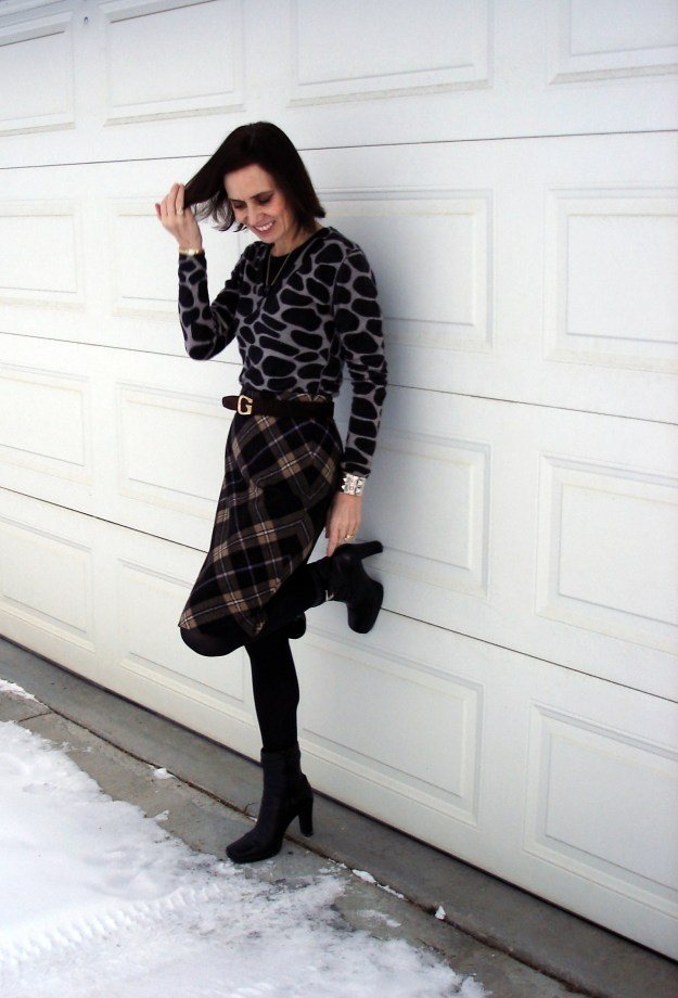 midlife fashion blogger wearing a business casual outfit with giraffe sweater and tartan skirt