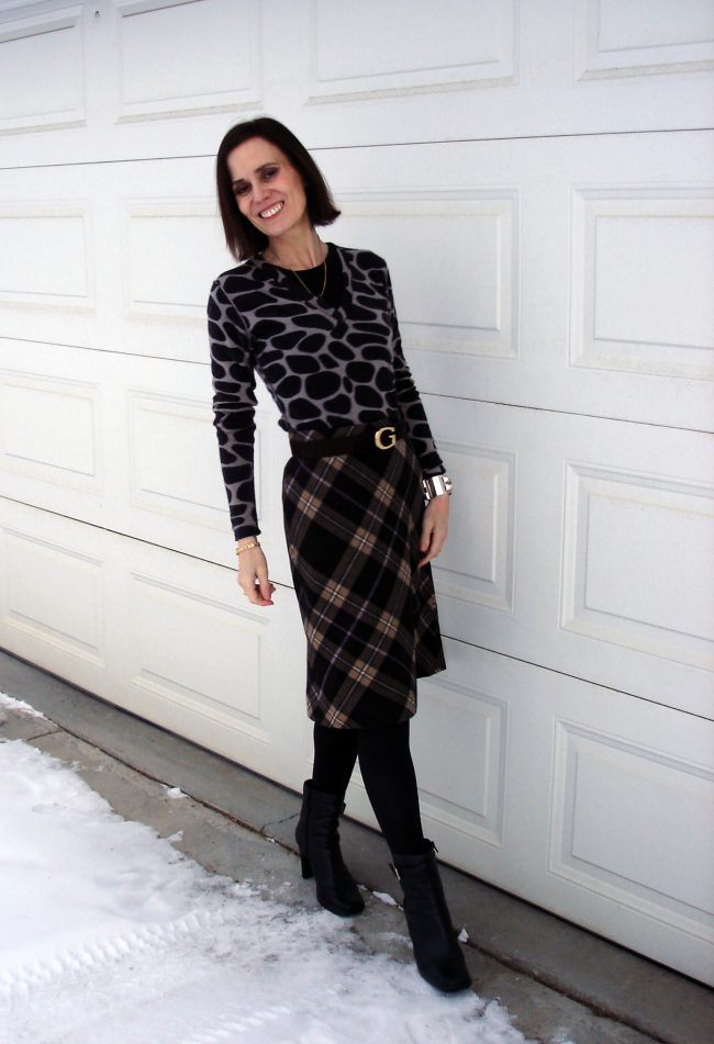 over 50 years olf woman wearing a diagonal plaid A-line skirt with giraffe print sweater
