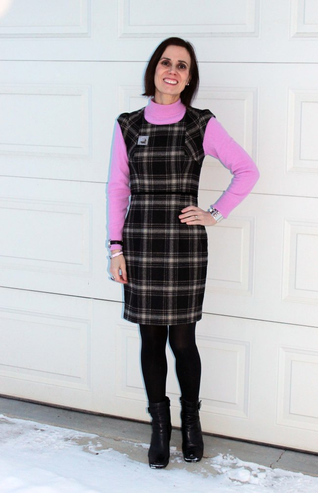 fashion blogger over 50 in plaid sheath with pink sweater