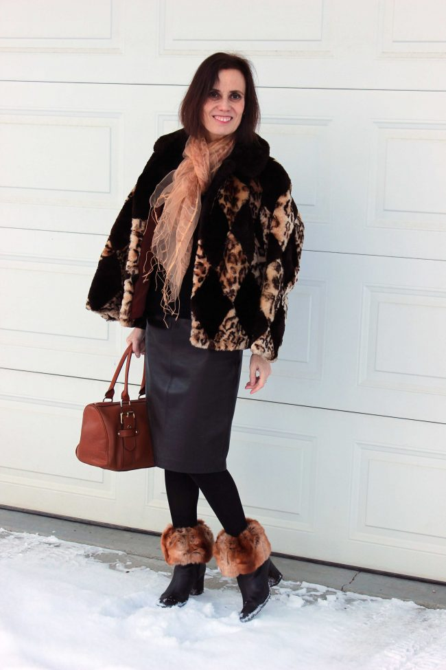 over 50 years old woman in leather skirt, tights, booties, faux fur top socks, diamond pattern jacket, scarf