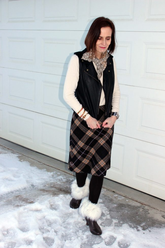 style blogger in layer outfit with vest plaid skirt sweater