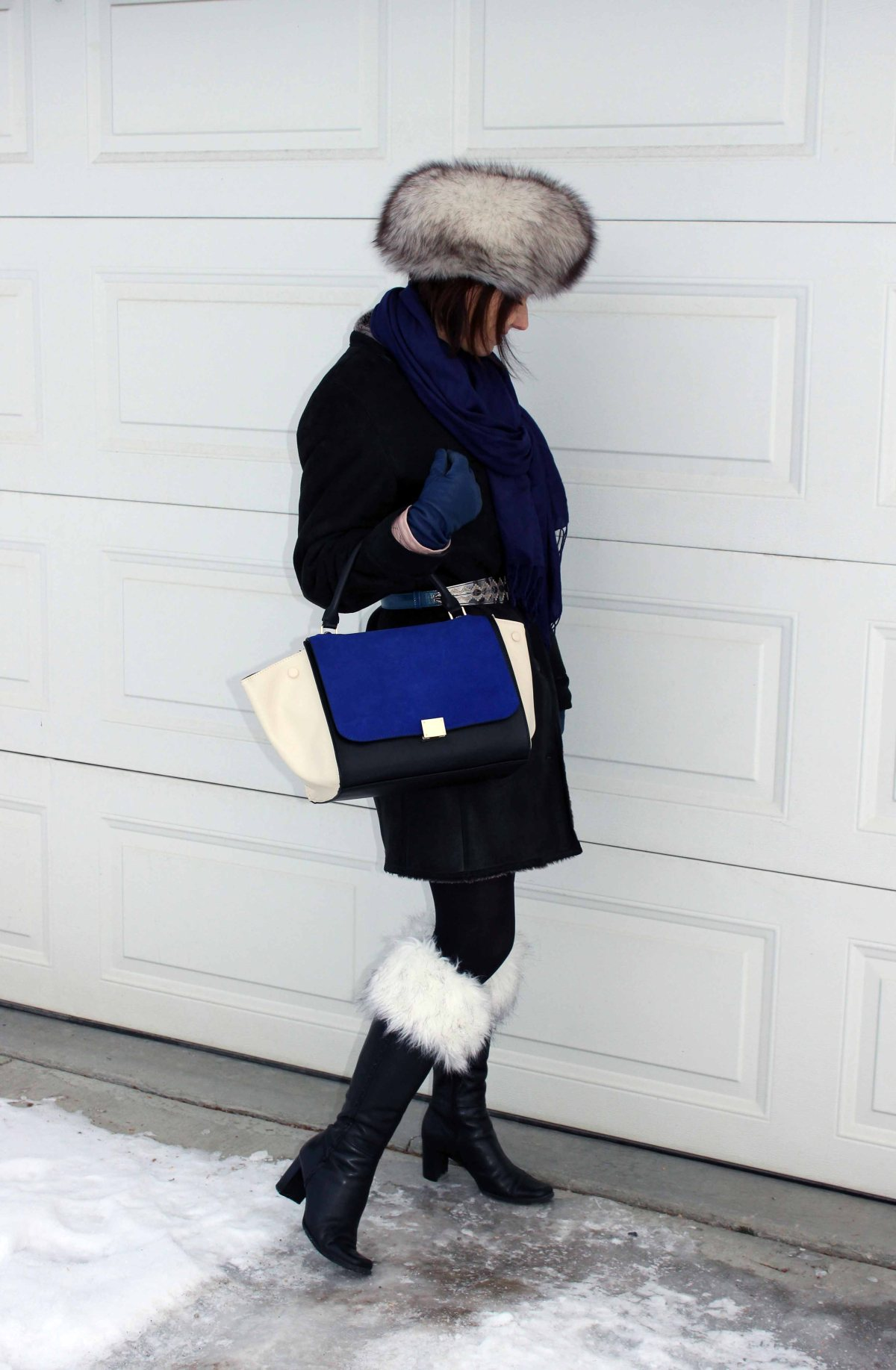 midlife blogger in shearling coat, accessorized galosches with statement bag and hat