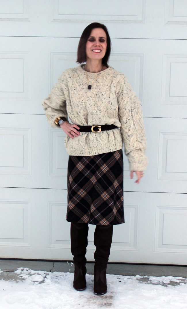 stylist in oversize cable knit sweater with bias plaid skirt