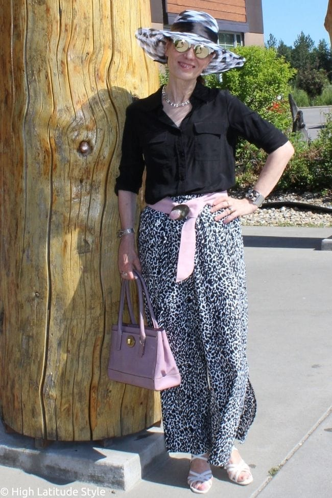 fashion blogger over 50 in pink, black and white look of hat, pants, shirt, sunnies