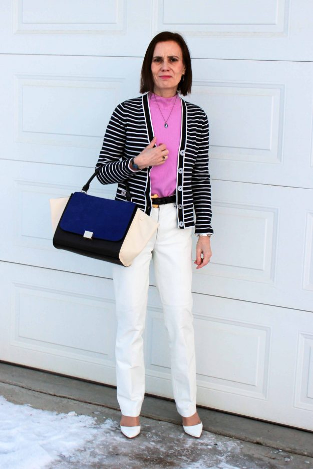 influencer in striped cardigan, white trousers pink sweater