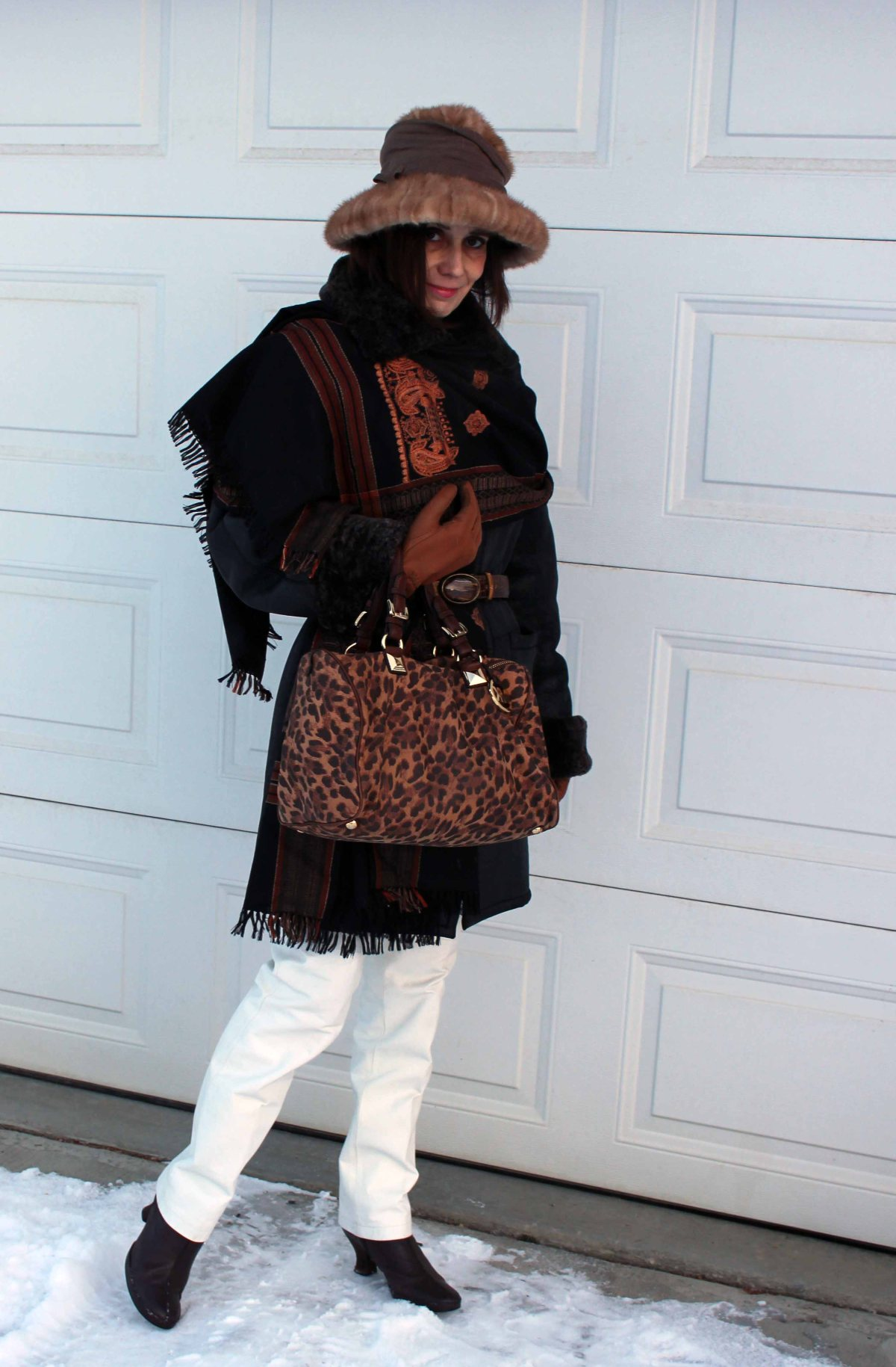 older woman in leather pants, shearling coat, Indian ethnic scarf, loafers and hat