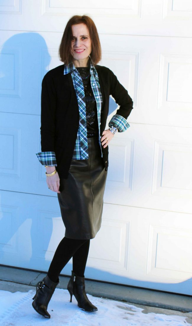 layering a green-blue-white-black plaid shirt over a sequin top and leather skirt outfit