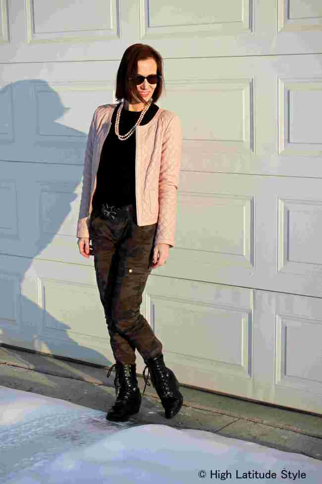 #styleover50 mature woman in street style chic with plush pink trend and camouflage cargos