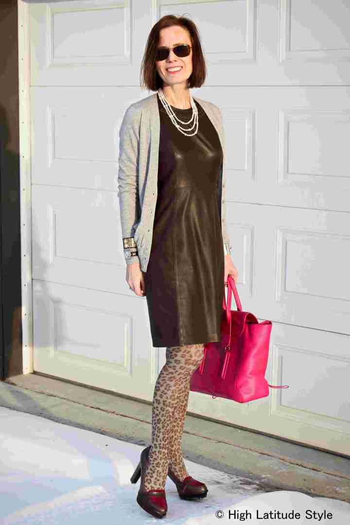 fashion blogger over 40 sporting a leather sheath with animal print legwear