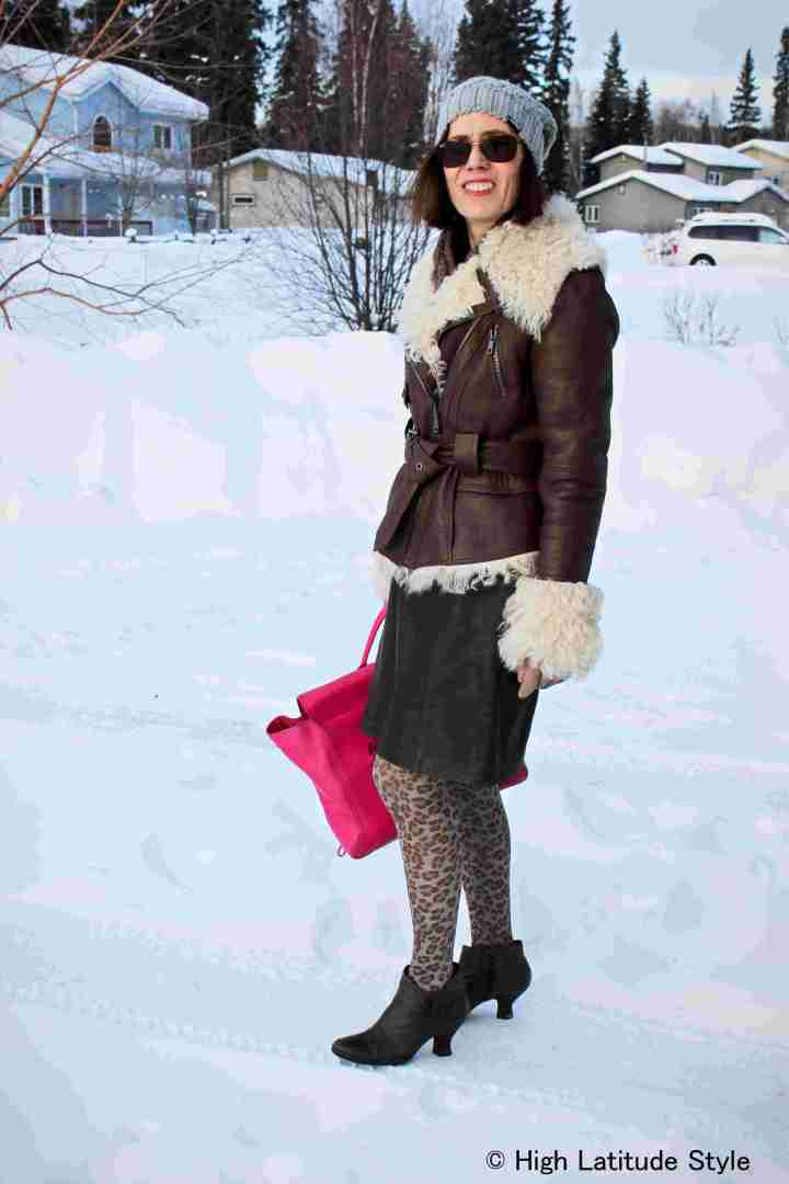 fashion blogger over 50 in brown and gray outerwear with leopard print pantyhose and fuchsia bag