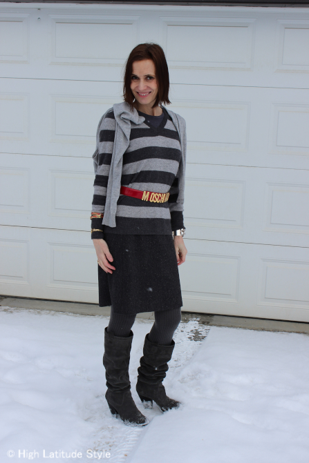 stylist in striped gray sweater, gray skirt, red belt