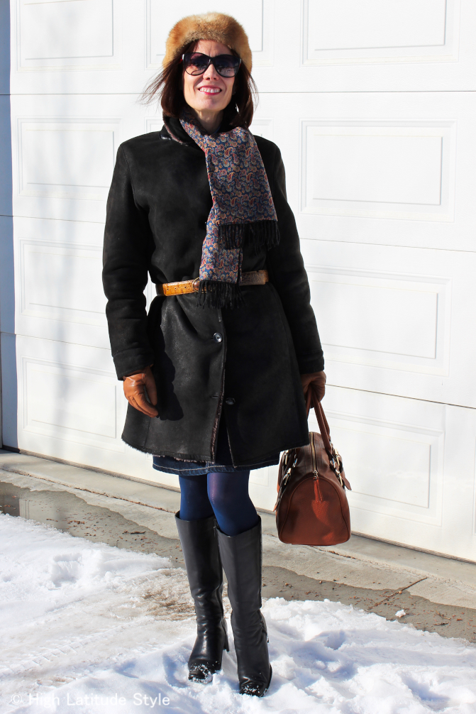 stylist in belted coat, matching tight, scarf, head band, riding boots
