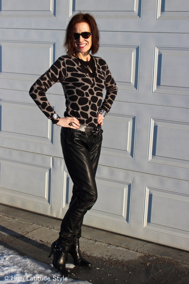 Nicole of High Latitude Style in animal print top and motorcycle booties with leather trousers posing in the snow