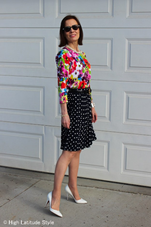 stylist in flower print top with polka dot pleated skirt