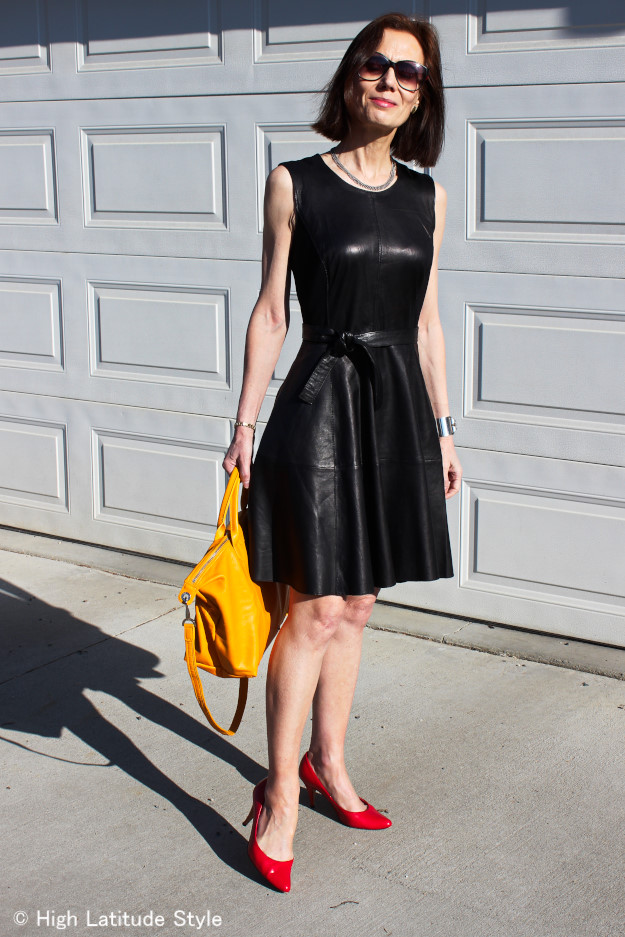 style blogger dancing in a fit-and-flare-leather-dress