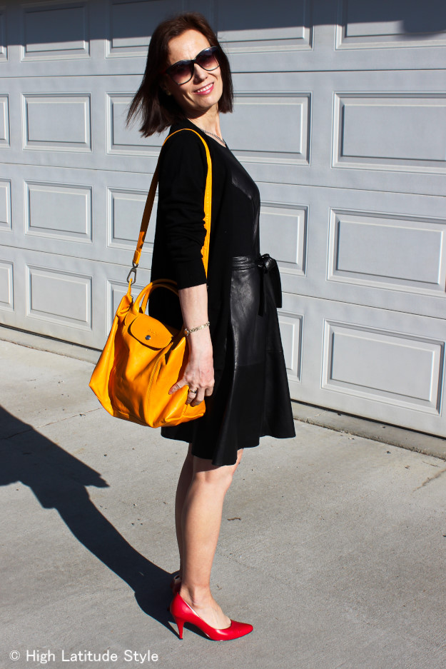 style influencer in fit-and-flare Leather Dress, red pumps, yellow bag