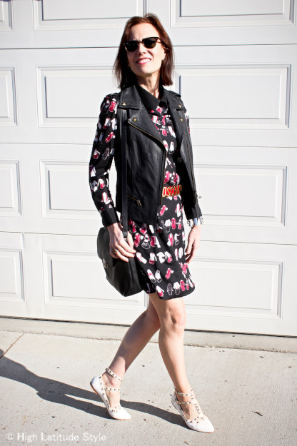 #fashionover50 midlife woman in concert attire with printed mini dress and studded leather vest