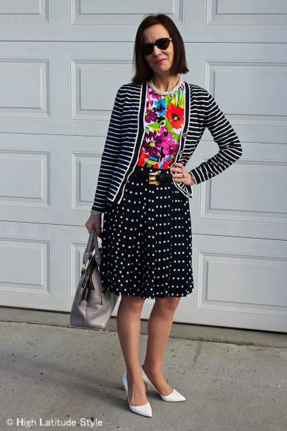 midlife style blogger in striped cardigan and floral top and polka dot skirt