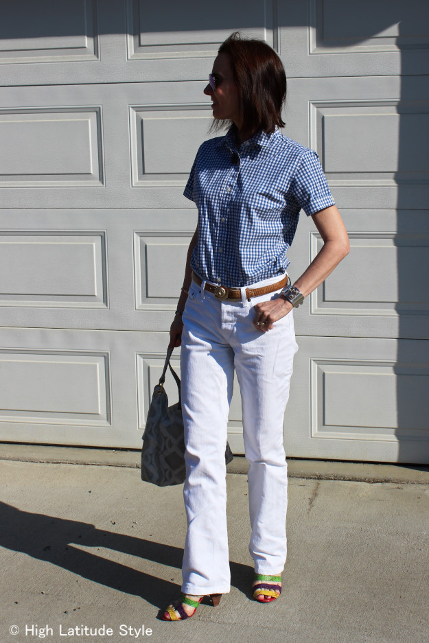 mature style blogger wearing a gingham shirt with white jeans