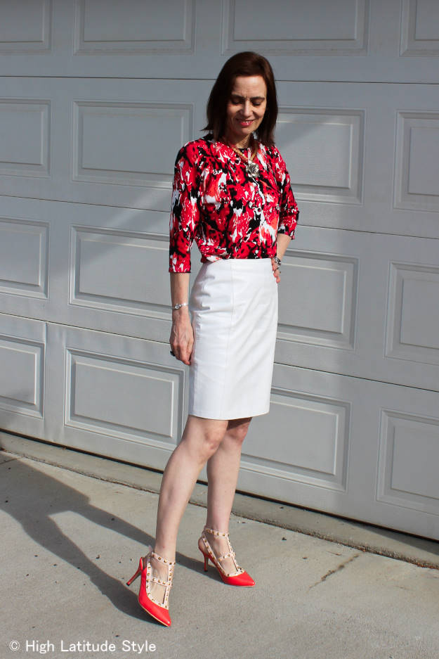 #fashionover40 woman in work outfit with abstract floral print cardigan and a white leather skirt