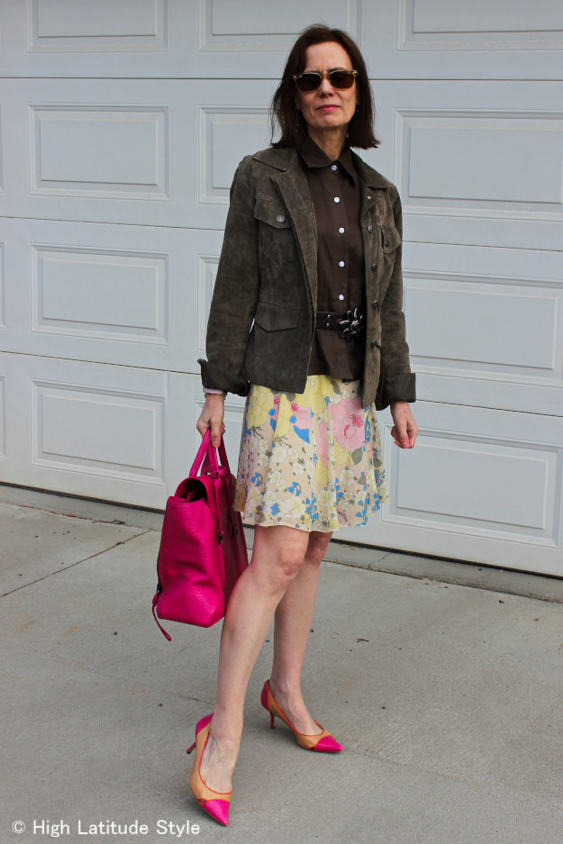 mature fashion blogger in floral skirt and suede utility jacket
