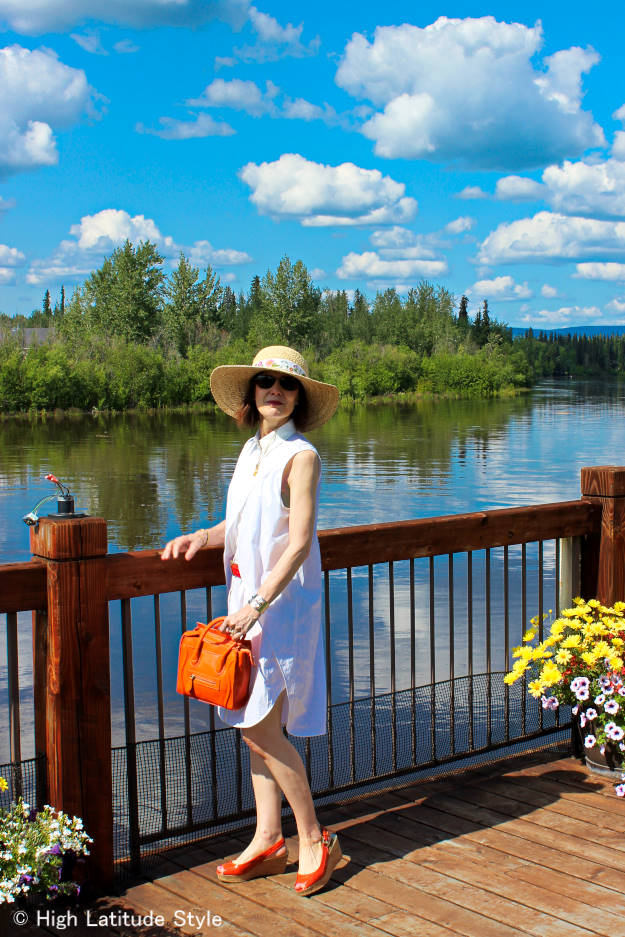 American woman in a little white dress with plateau footwear, belt and sun hat