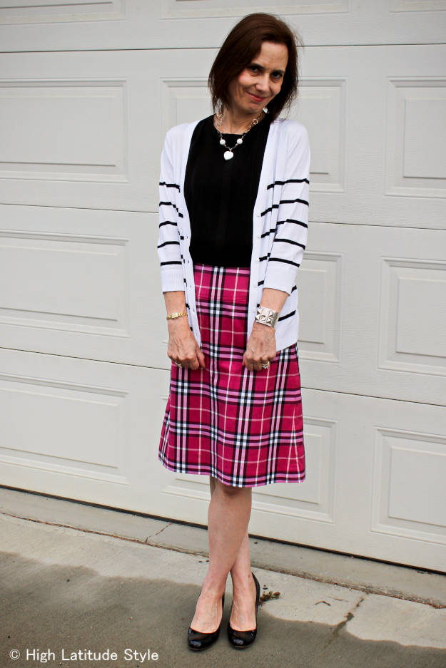 older woman looking posh chic in a rose, black and white Burberry plaid bottom, black top and black and white necklace