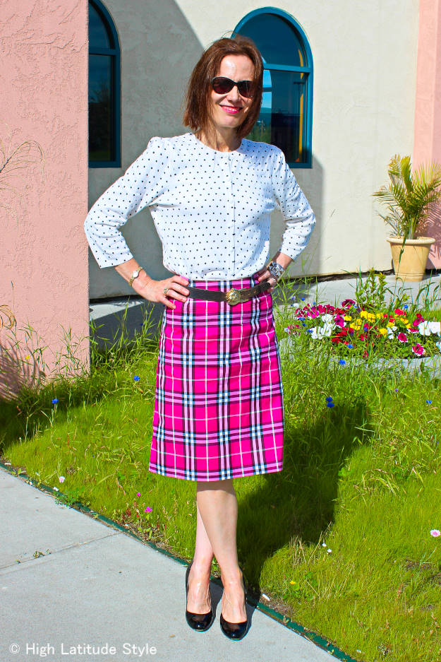 older woman in a Burberry pink plaid skirt and polka dot top