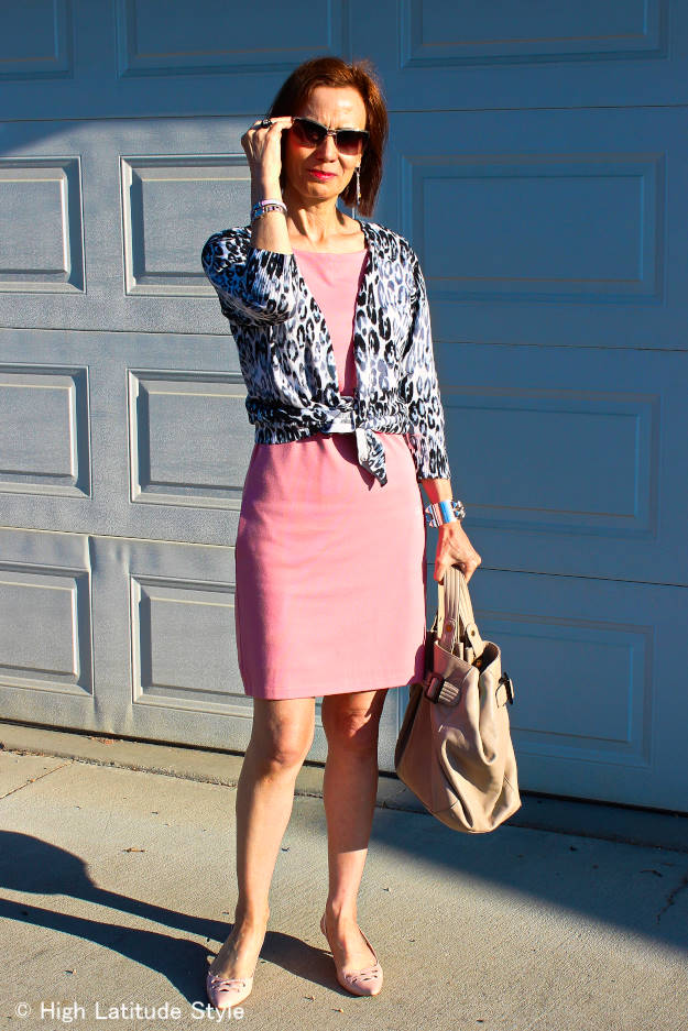 midlife woman in cardigan and blush sheath dress