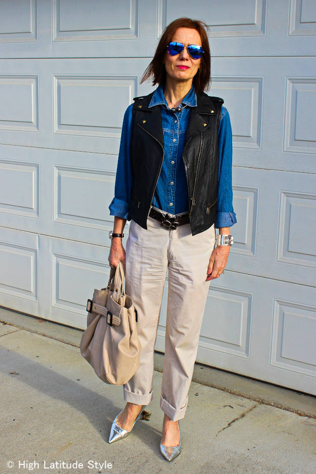 street style blogger with denim shirt, leather vest, sunnies, and silver pumps