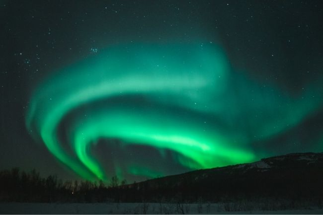 green aurora over hill and snow