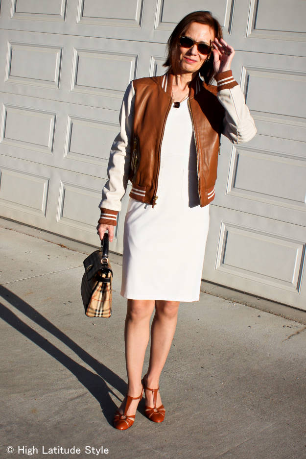 midlife woman in posh chic sheath with baseball jacket