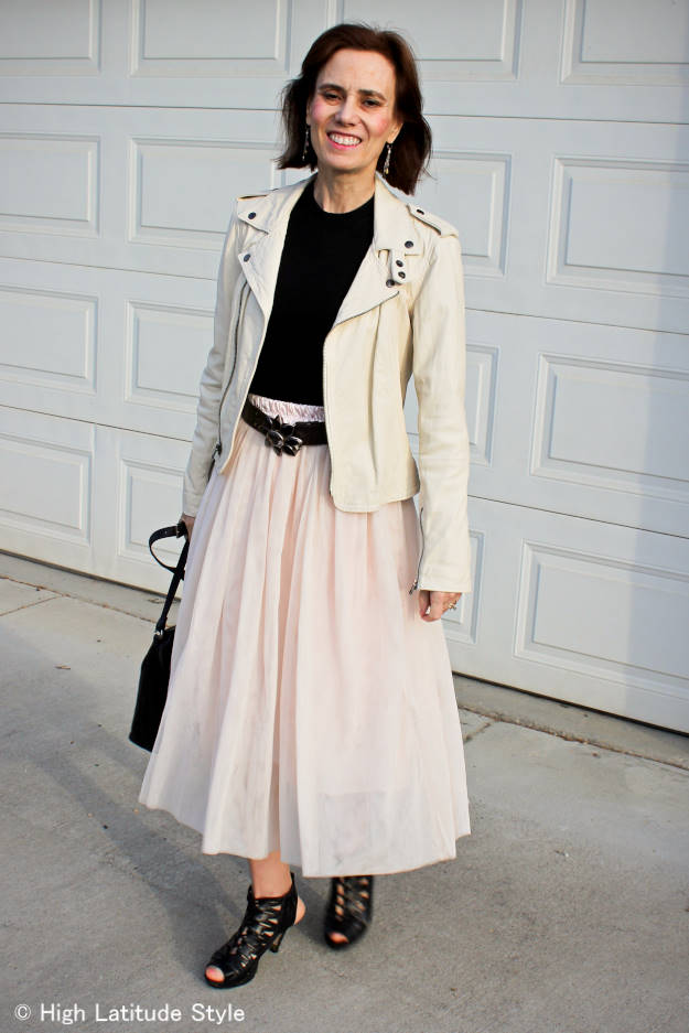 #over50style High Latitude Style donning a fall outfit with pastel skirt and moto jacket plus black top and fall sandals