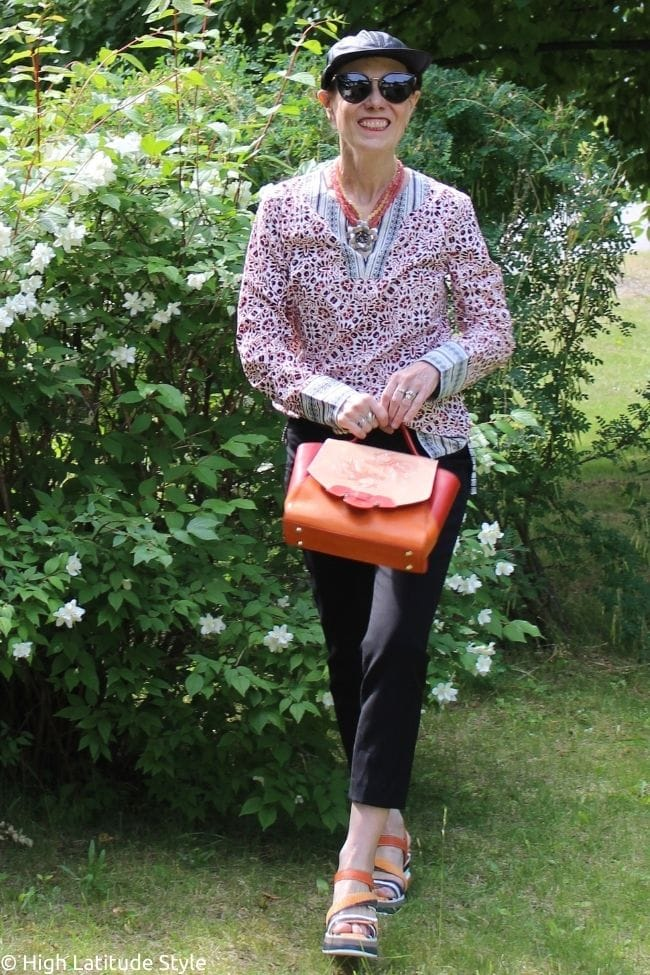 style book author in back yard BBQ potluck outfit with cropped pants, tunic, sandals, baseball hat and bag