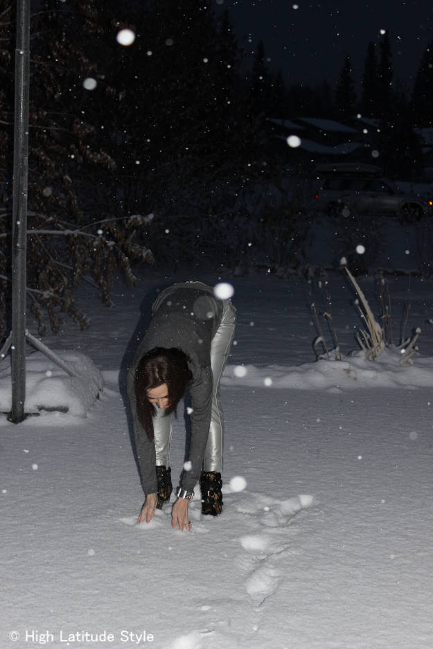 #fashionover40 bending down to pick up snow