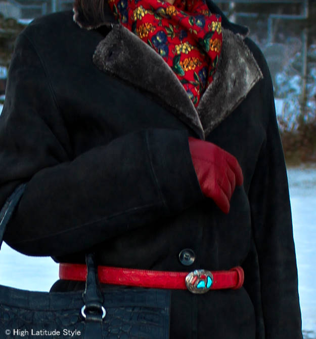 Zoom-in on the styling of the outerwear. The ethnic belt buckle picks up colors of the scarf and stays in the red theme of the accessories