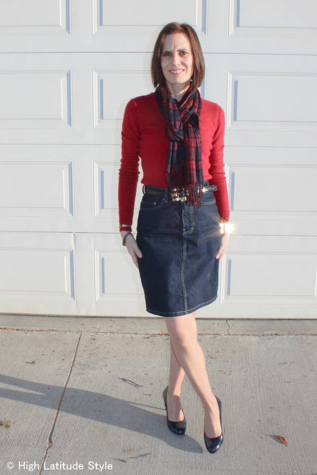 fashion blogger over 50 in casual work look with denim skirt and consigned sweater and belt