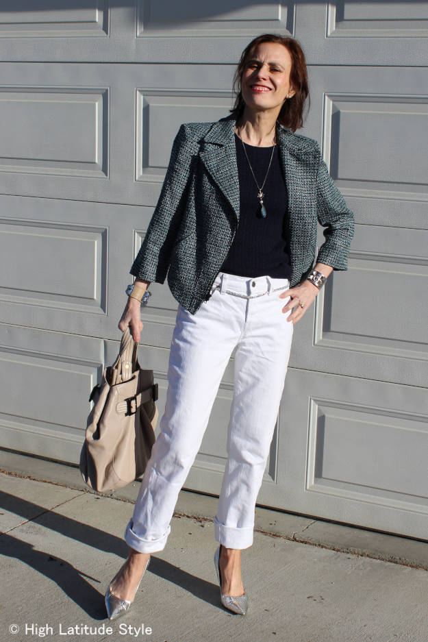 #styleover50 mature woman in casual outfit with tweed motorcycle jacket, cable knit sweater, bag, DITY jewelry and silver pumps