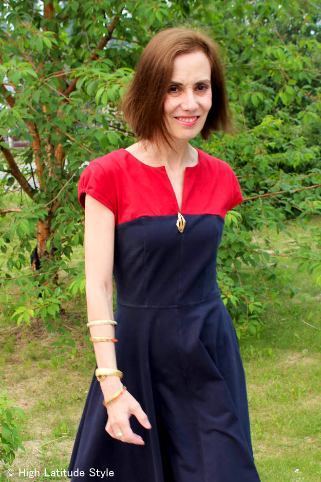 #over50fashion woman looking stylish in a color blog dress styled with a pin at the cleavage