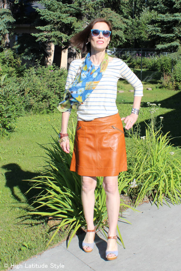 stylist mixing prints and patterns with tan leather skirt striped top floral scarf