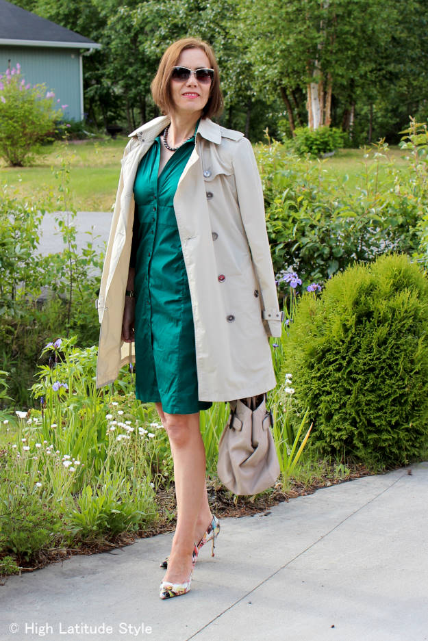 style blogger in a Burberry Brit trench coat with thrifted shirt dress, floral pumps, and black pearl necklac