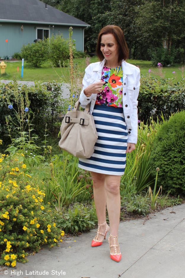 style book author in white denim jacket, floral cardigam studded pumps and striped skirt,