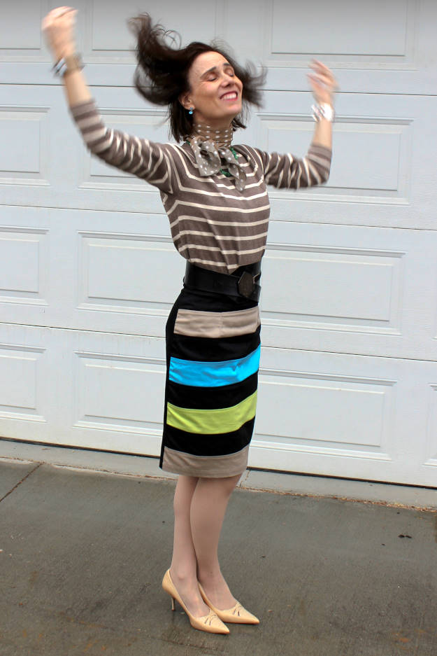 over 50 years old fashion blogger in stripped sweater and striped skirt in the rain