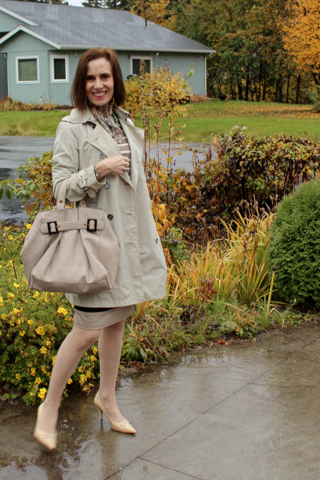 style book author in trench coat and striped sweater and skirt standing in the rain