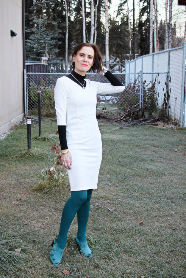 older fashion blogger wearing a fitted sheath dress with tights, sandals and jewelry