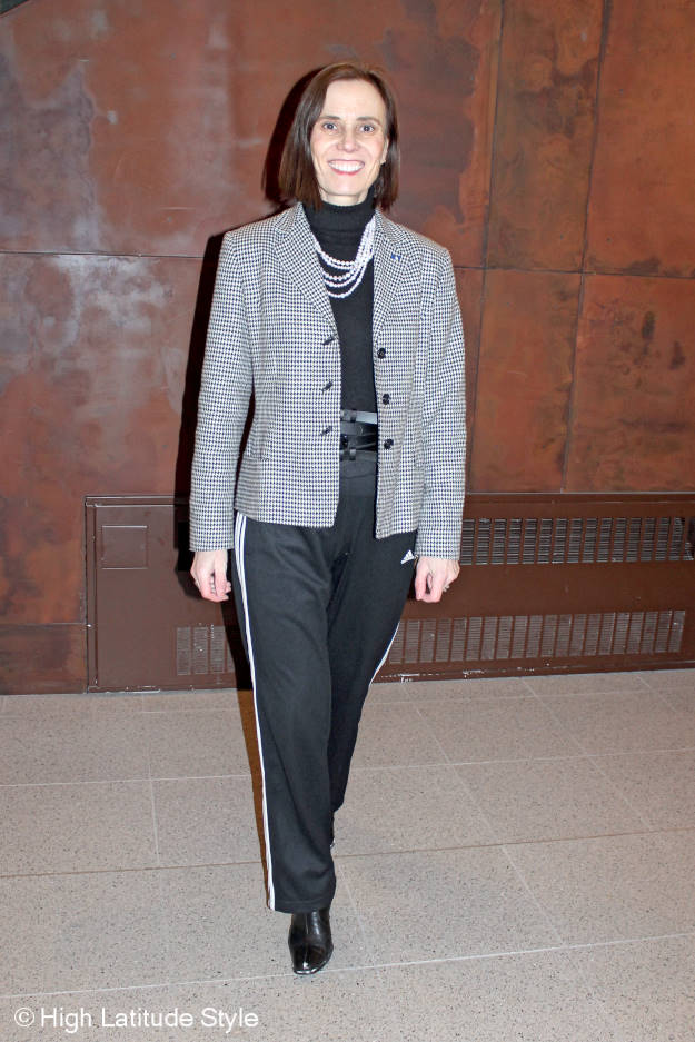 mature woman dressed in an athleisure pants and business casual jacket accessorized with pearls