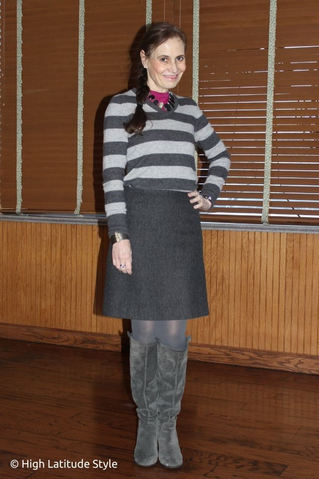 stylist in gray skirt with striped top, pink layering top