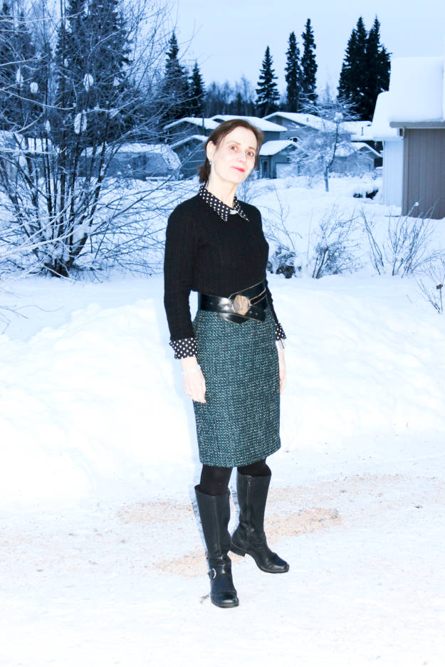 stylist in winter work outfit with tall black boots, skirt, and polka dot shirt